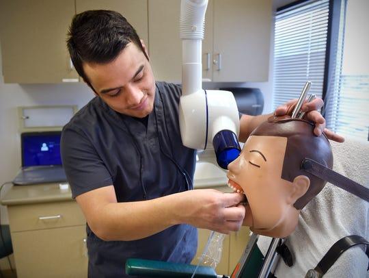 Dental Hygenist student Edson Salgado practices taking