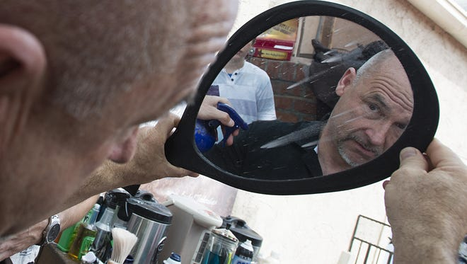 Grego Yturiaga takes a look in a mirror after receiving a shave on the patio of the Silver Grill Cafe in Old Town Sunday, June 21, 2015.