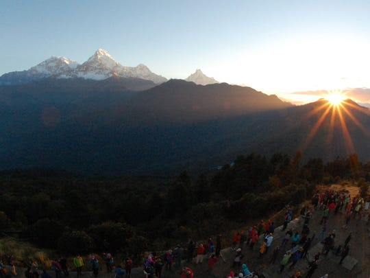 In this Friday, Oct. 24, 2014 photo, the sun rises above the Annapurna Range in central Nepal as viewed from Poon Hill, above the village of Ghorepani. Poon Hill, the highest point of the six-day, 65-kilometer (40-mile) loop through the villages of Ghandruk and Ghorepan can be crowded with other trekkers at sunrise during peak trekking season.