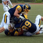 Making the play for South Lyon's defense in Friday's season opener against Pinckney are a trio of tacklers, led by Ryan Pedersen (top), Jeff Gill (right) and Leonard Morgan.