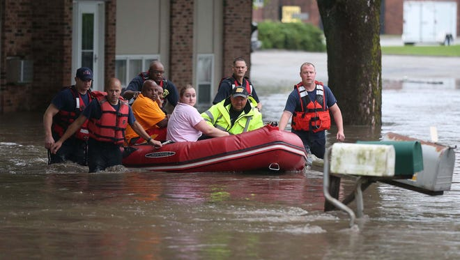 Local fire departments including Clive and Ankeny evacuate a group of people stuck in apartments at 1275 Northwest 75th Street in Clive on Thursday morning, June 25, 2015. The group of people were left stranded in the apartment building by the quickly rising waters of Walnut Creek.