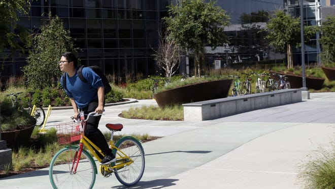 In this June 5, 2014 photo, a man rides a bike past a Google sign at the company's headquarters in Mountain View, Calif. Google's earnings were well below analysts' predictions, Thursday, Jan. 29, 2015, marking the fifth consecutive quarter that Google Inc. hasn't cleared a key hurdle for publicly held companies. (AP Photo/Marcio Jose Sanchez) ORG XMIT: NYBZ325