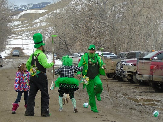 Dan Joyce and Carla Hankins dance a jig during the Square Butte St. Patrick's Day parade as the other member of the Hooligan Party, Justin Roudebush, looks on. He's carrying a hoe as he campaigned for the position of Square Butte professional hoer.