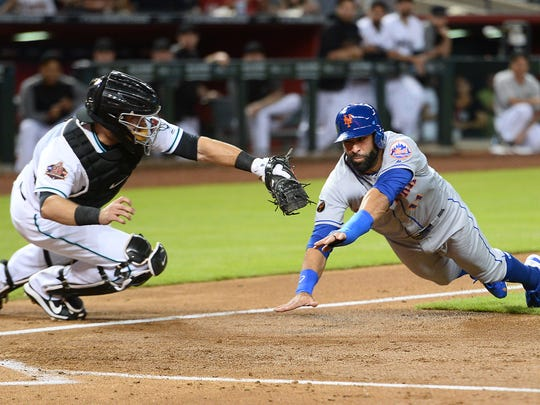 New York Mets center fielder Jose Bautista (11) is tagged out by Arizona Diamondbacks catcher Alex Avila (5) trying to score on a fly ball during the second inning at Chase Field.