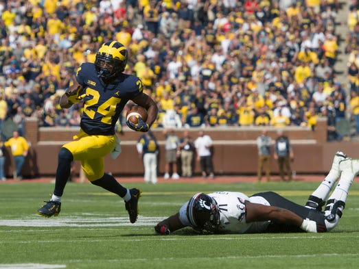 Michigan defensive back Lavert Hill runs away from