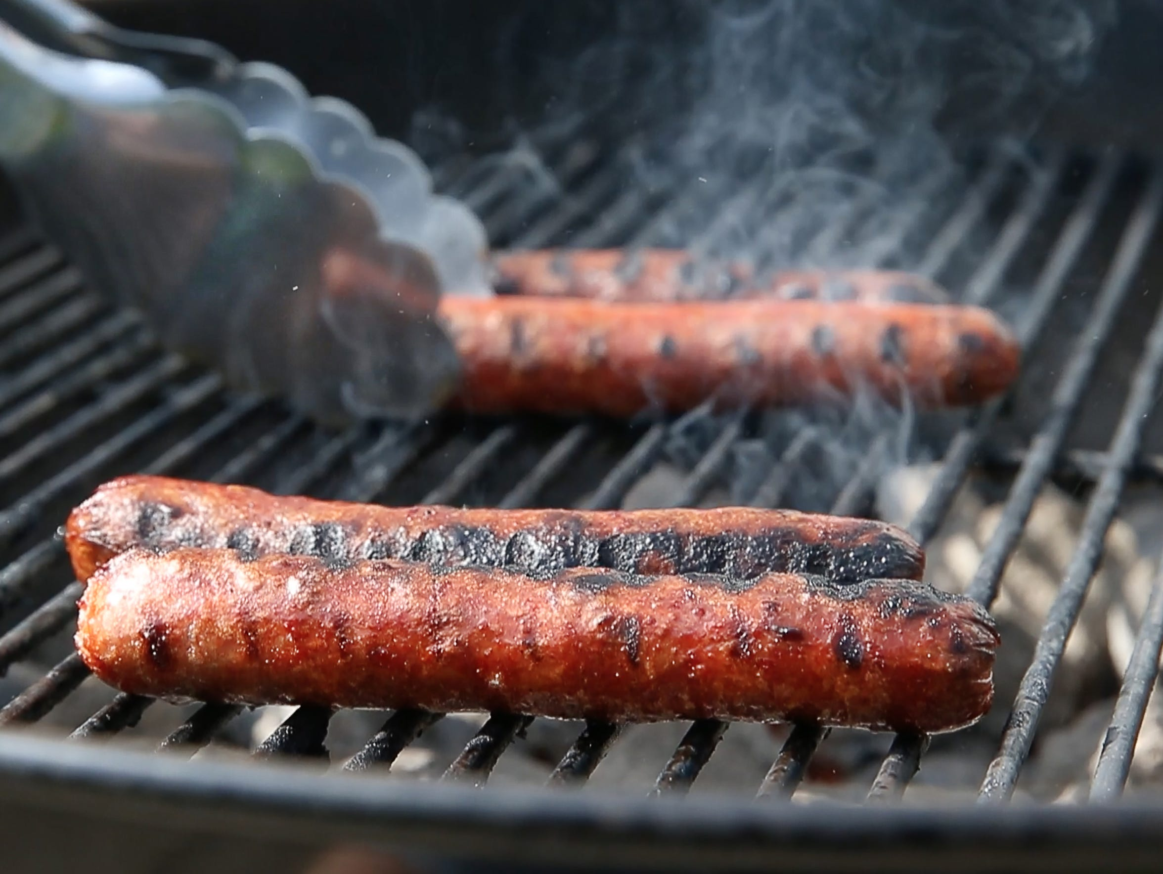 Hot dogs were grilled on a hot charcoal grill.
