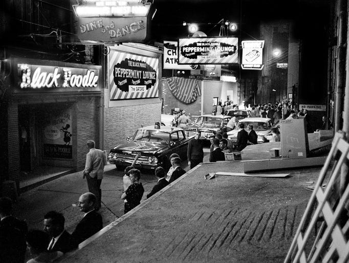 Hundreds of curiosity-seekers mill around the entrances of Printers Alley night spot during a raid in 1962. They arrested 16 people and confiscated some 700 bottles of liquors.
