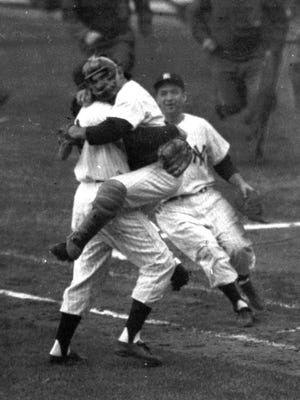 Yankees catcher Yogi Berra leaps into the arms of Don Larsen after Larsen pitches a perfect game in the 1956 World Series.