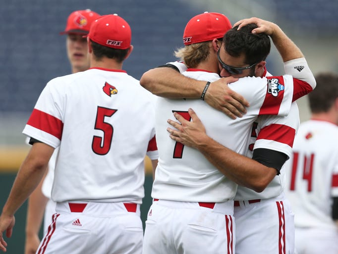 Louisville senior Jeff Gardner hugs junior Grant Kay (7) after the Cards were eliminated from the 2014 College World Series by Texas.  June 16, 2014
