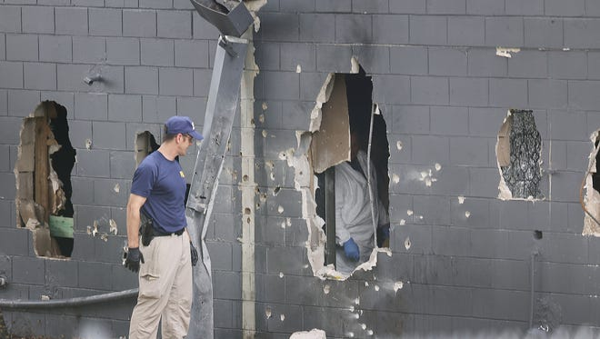 FBI agents investigate near the damaged rear wall of the Pulse Nightclub on Sunday, June 12, 2016. Omar Mateen, 29, was killed by police when he engaged them in a gun battle. Forty nine people were killed at the Orlando nightclub.