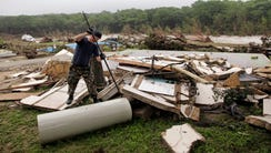 Kevin Calaway pries apart debris from a cabin shattered