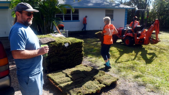 """Robert Gingras, an Air Force veteran, looks on as volunteers from The Home Depot in Sebastian sod portions of his front yard on Thursday, Jan. 11, 2018, in Vero Lake Estates. The needed yard work was funded by The Home Depot Foundation, which partnered with the Veterans Council of Indian River County. """"During the summertime, I'm underwater here. There's a river on the side of the house, a lake in the back and a pond behind the workshop,"""" Gingras said of his experience during the rainy season. """"It's really great to have these volunteers come out and help me."""""""