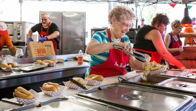 Yolanda Capriglione serves up porkette sandwiches at the Italian Festival at Saint Anthony of Padua Church in Wilmington last Sunday.
