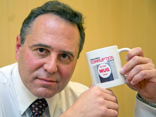 In this Nov. 19, 2015 photo, In this Nov. 19, 2015 photo, Bruce Roter, founder and president of the Museum of Political Corruption, poses with a mug in Albany, N.Y.