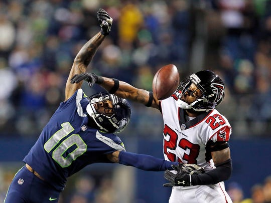 Seattle Seahawks' Paul Richardson, left, misses catching the ball as Atlanta Falcons' Robert Alford defends in the second half of an NFL football game, Monday, Nov. 20, 2017, in Seattle. (AP Photo/Stephen Brashear)