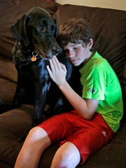 """In this Sept. 8, 2015 photo, Jack Baker hugs his father's PTSD service dog, Honor, at his home in Clyde, N.C. """"He's the last connection that the boys have with their father,"""" says Nicole Shumate, executive director of Paws & Effect. """"And I'm sure if we gave the dog the choice, he'd prefer not to be uprooted."""""""
