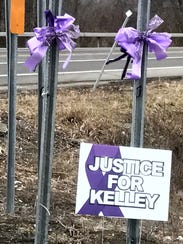 Signs and purple ribbons in memory of murder victim
