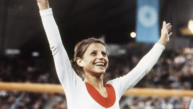 In this Aug. 1972, file photo, Olga Korbut, of Russia, throws up her arms in joy at the 1972 Summer Olympics in Munich, Germany, Aug. 1972.