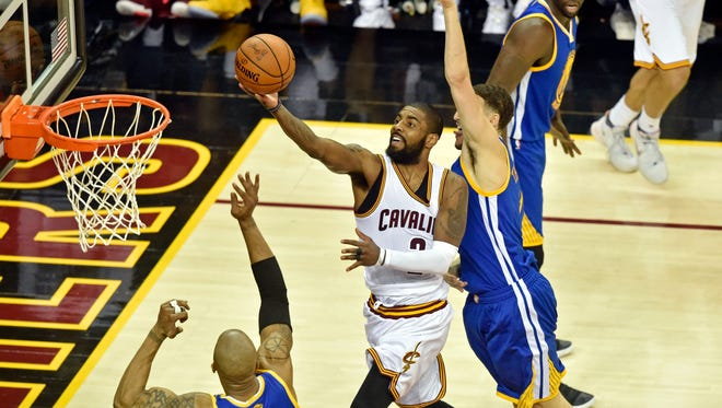 Cleveland Cavaliers guard Kyrie Irving (2) shoots the ball against Golden State Warriors forward David West (3) during the second quarter in game four of the Finals for the 2017 NBA Playoffs at Quicken Loans Arena.