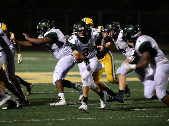 Groves senior quarterback Colton Tinslely sets to hand off to senior tailback Chaise Ford in Friday's three-OT thriller at Harrison.