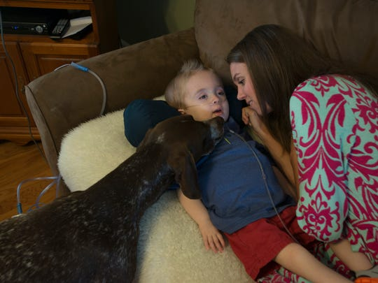 The family dog Gauge pokes his head up to give Porter Heatherly and mommy Sara some love. Porter, who is nearly 3 years old, has a rare condition called GM1 gangliosidosis, type 1, an inherited disorder that progressively destroys nerve cells in the brain and spinal cord and causes multiple seizures each day.