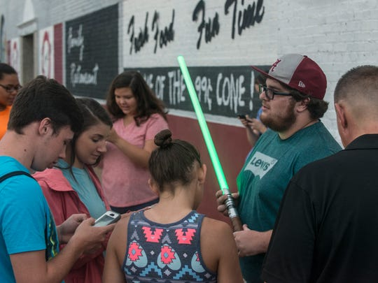 Andrew Jenkins can't play Pokemon Go because it won't download on his phone, but he did bring his lightsaber. Pokemon Go players pack downtown Prattville  with their phones and other mobile devices trying to catch Pokemon and battle each other on Thursday, July 14, 2016.