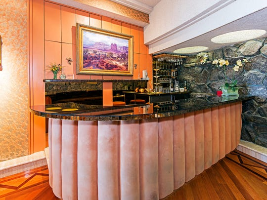 The wet bar in the main dining room is faced in puffy panels of pink suede.