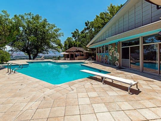 The pool area features mosaic murals by Les Garcia, the builder and first owner of the estate. The entertaining cottage is at rear.