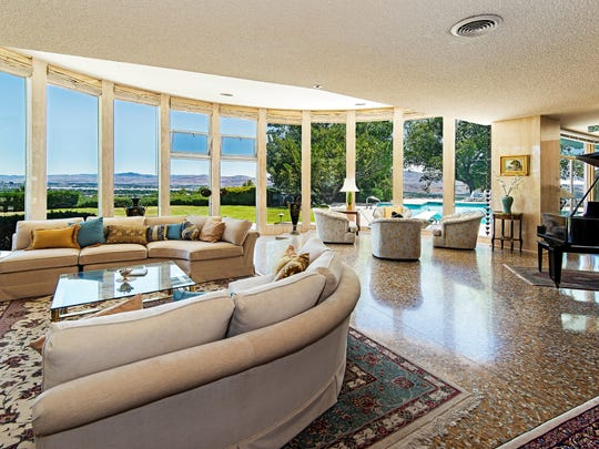 The living room in the main residence features a curving wall of windows and travertine marble floors.