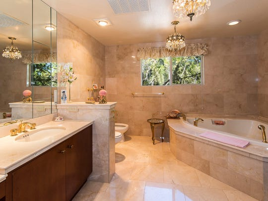 Her master bathroom, part of the lavish master bedroom suite, offers floor-to-ceiling marble, chandelier lighting and a deep soaking tub.