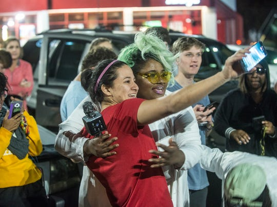 Katie James, left, takes a selfie with singer Ashley Nicole, who brought a group of angel singers with her to perform a Taco Bell song. Dozens gathered Sunday night in Montgomery on Zelda Road in the ArbyÕs parking lot for a candlelight vigil for the Taco Bell next door, which caught fire Wednesday. The whole thing began as as a Facebook event joke posted by Katie James of Montgomery that drew the attention of thousands.