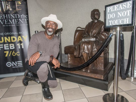 "Isaiah Washington, who plays E.D. Nixon in a new movie, kneels next to a statue of Rosa Parks. The first official screening of TV One's film ""Behind the Movement"" was shown to a packed house Thursday, Feb. 1, 2018, in the auditorium of the Rosa Parks Museum in Montgomery, Ala. The film on Rosa Parks and the Montgomery Bus Boycott will air Feb. 11 on TV One."
