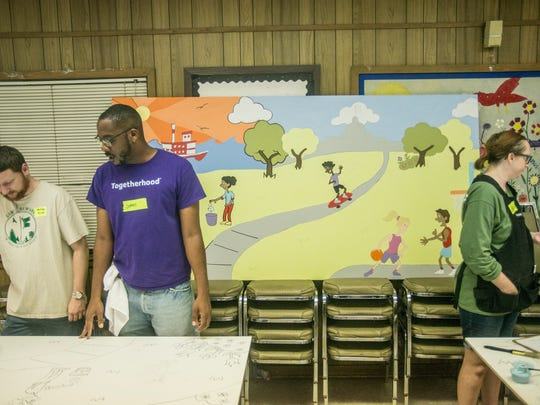 A completed version of the murals is displayed in the background. Volunteers gathered at the E.D. Nixon Community Center on Saturday, June 23, 2018, to paint by numbers on nine murals for Montgomery schools.