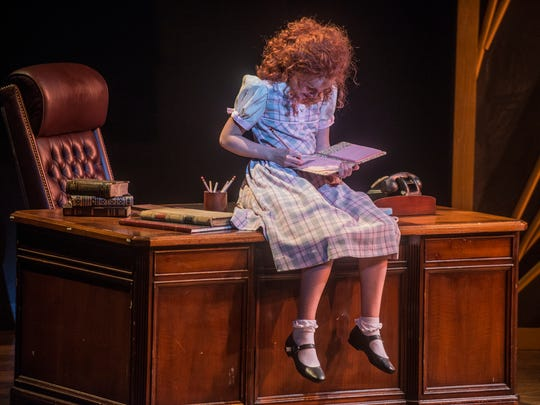 Vivian Poe sits on Warbucks' desk as the title character