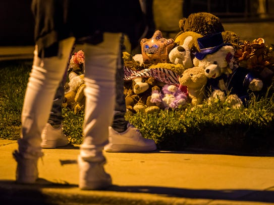"Friends of Keshall ""KeKe"" Anderson look at stuffed animals and balloons left near the spot where she was killed along W. 20th Street in Wilmington at a vigil commemorating her 20th birthday in 2016."