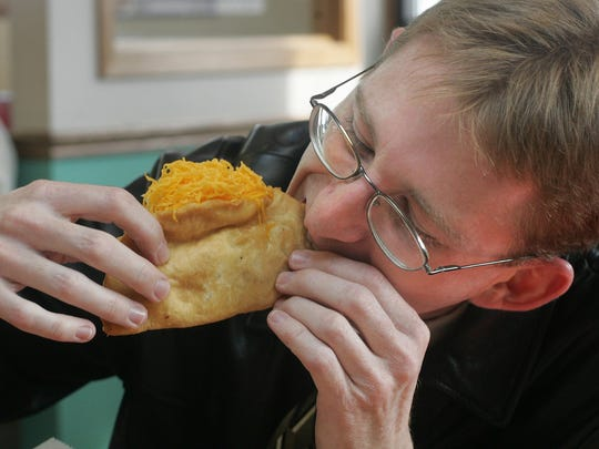 Eric Wildman dives into lunch at Tasty Tacos location on East Grand Avenue in Des Moines.