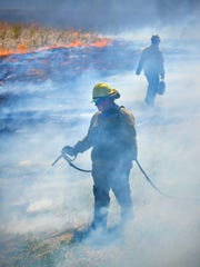 Hannah Tuntland, left, and Tyler Thorndal of Minnesota Native Landscapes control the edges of the burn Wednesday, May 4, as they burn 36 acres of prairie around Kennedy Community School in St. Joseph.