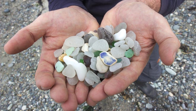 Tim Blair holds a handful of his collection from a day on Glass Beach.