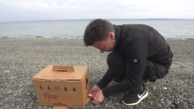 Jon Liebling, owner of Firetote, a new Bainbridge business, lights one of his boxes on the beach at Fay Bainbridge Park.