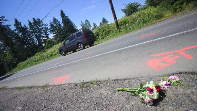 FILE PHOTO – Flowers lay along Finch Road on Bainbridge Island near where two joggers were hit by a vehicle on June 17.