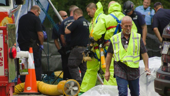 Police and fire crews work to pull a body out of a sewer line in Lansing. The body was discovered by a public service employee at about 10 a.m. Aug. 21, 2018.