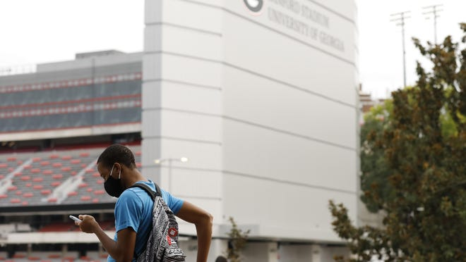 A University of Georgia student waits for the bus outside the University's Tate Student Center in Athens, Ga, on Wednesday, Sept. 16, 2020. The university reported a total of 421 positive tests for COVID-19 infections for the week of Sept. 7-13. Almost all (404) were students.