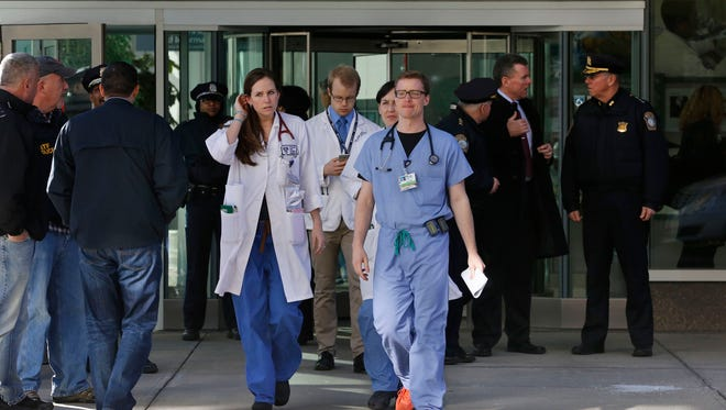 Medical personnel walk past law enforcement officials, right, as they depart the site of a shooting Jan. 20, 2015, at Brigham and Women's Hospital, in Boston.