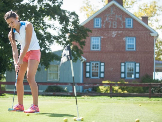 Melissa Kulcyk of Marlton warms up Friday on the Indian Spring Country Club's practice putting green next to the Center for the Arts in Southern New Jersey (right). Below: Despite a 'Public Welcome' plaque on the club's sign, many think the Evesham-owned club is members-only.