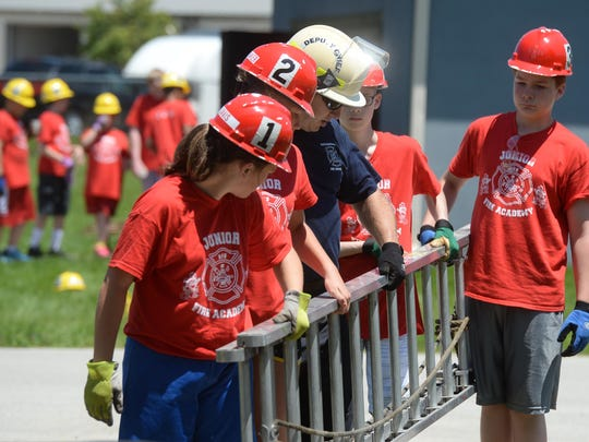Junior Fire Academy participants learn skills including, climbing ladders, rescuing and extracting victims Wednesday during the Richmond Fire Department summer camp in Richmond.