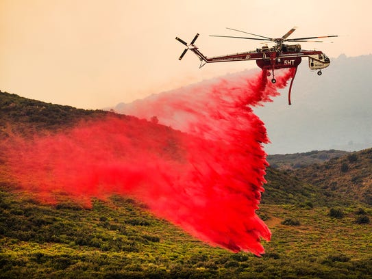 A helicopter drops retardant near the Goodwin Fire