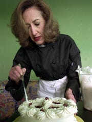 Susan Turner adds some finishing touches to one of her cakes, circa 2001.