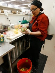 Salad bar clerk Lolita Oakley sorts through some of