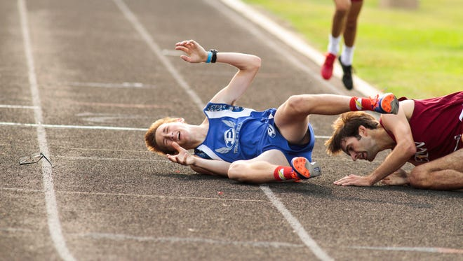 Erath's Ethan Suire, left, and E.D. White's Stephen Boudreaux on the ground after falling at the finish of the 1600 Thursday at the 3A regional meet at Wildcat Stadium in Abbeville.