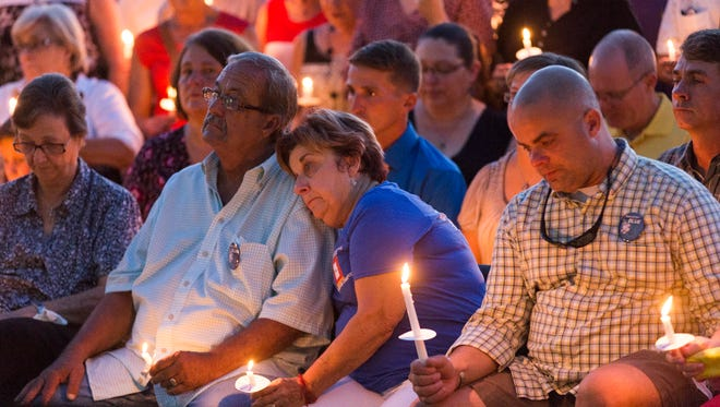 Patricia Gerald, mother of Matthew Gerald-  one of three Baton Rouge police officers killed in a July 17 shootout, leans on her husband, Ronnie, during a candlelight vigil for Gerald in Baton Rouge July 18.